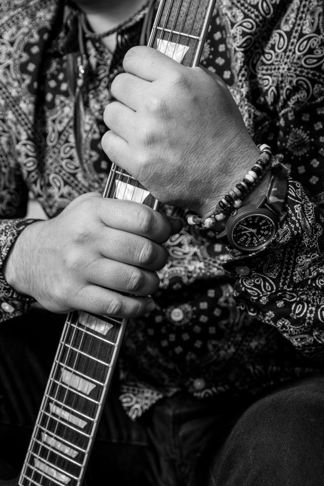 Hands holding guitar neck